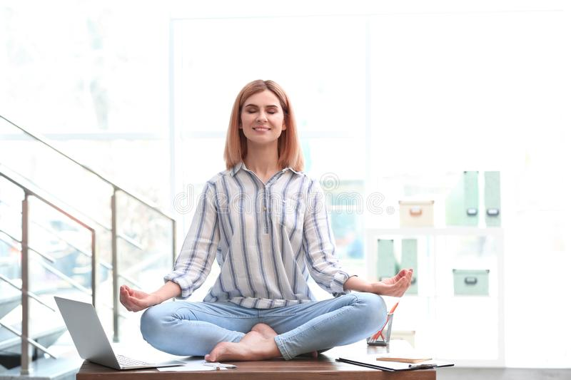 Beautiful woman meditating on table in office. Zen yoga stock photo