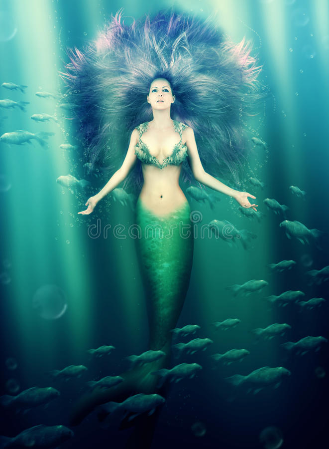 Beautiful woman mermaid in the sea. Fantasy. beautiful woman mermaid with fish tail and purple hair swimming in the sea under water royalty free stock images