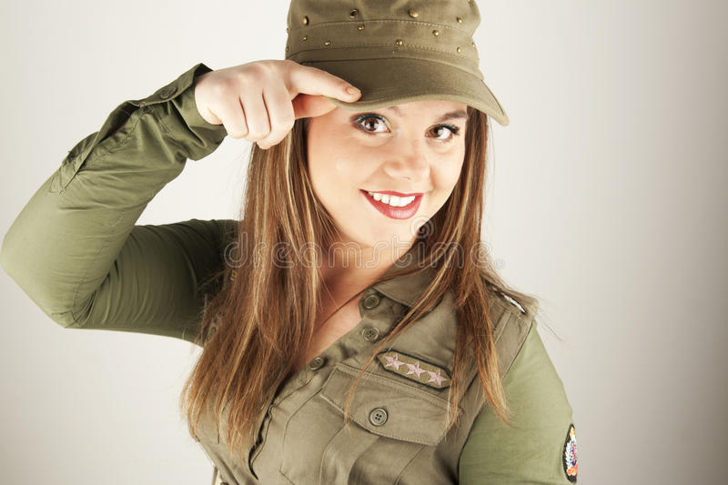 Beautiful woman in military clothes saluting royalty free stock photo