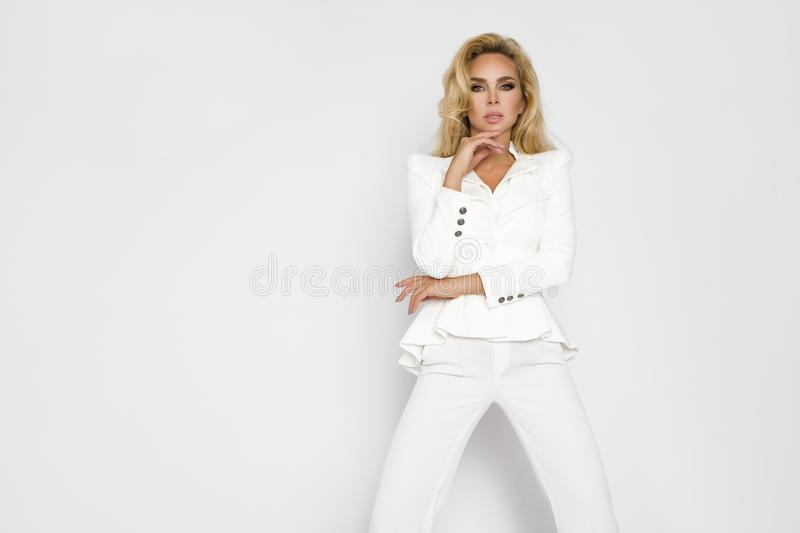Beautiful woman with long blond hair, dressed in elegant,white spring clothes. royalty free stock image
