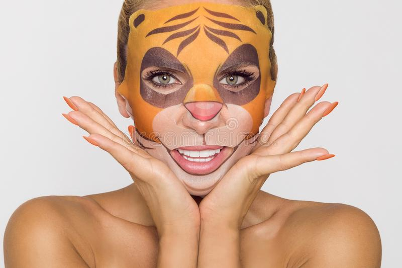 Beautiful woman with moisturizing leopard face mask. Mask with leopard, cat. Beautiful woman model girl with moisturizing leopard face mask. Mask with leopard royalty free stock images