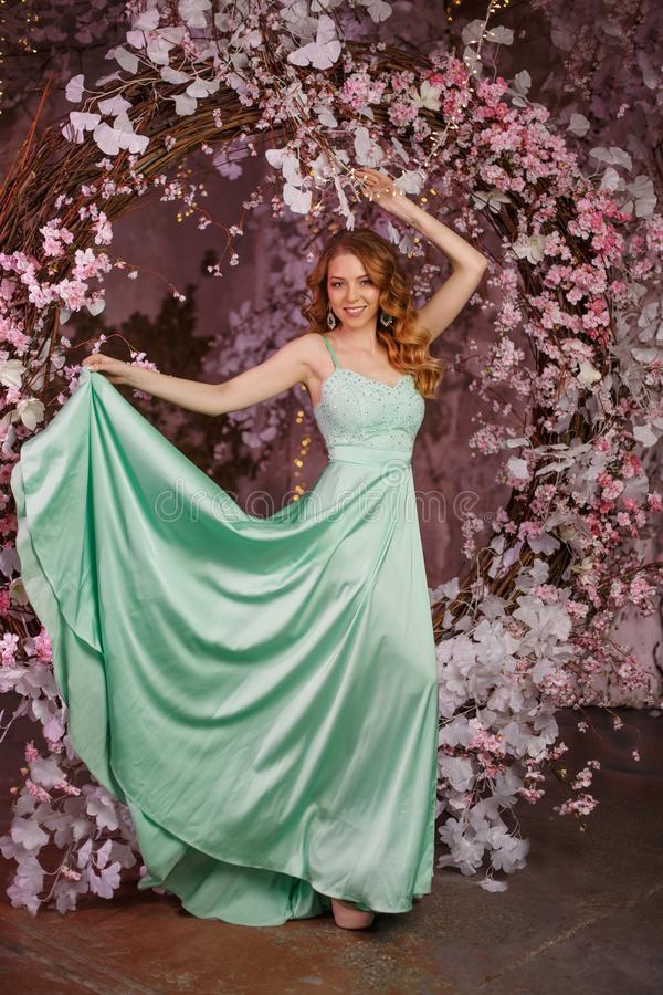 Beautiful woman model in a mint-colored dress on a flowered spring background. Beauty girl with a stunning makeup and hairstyle stock image