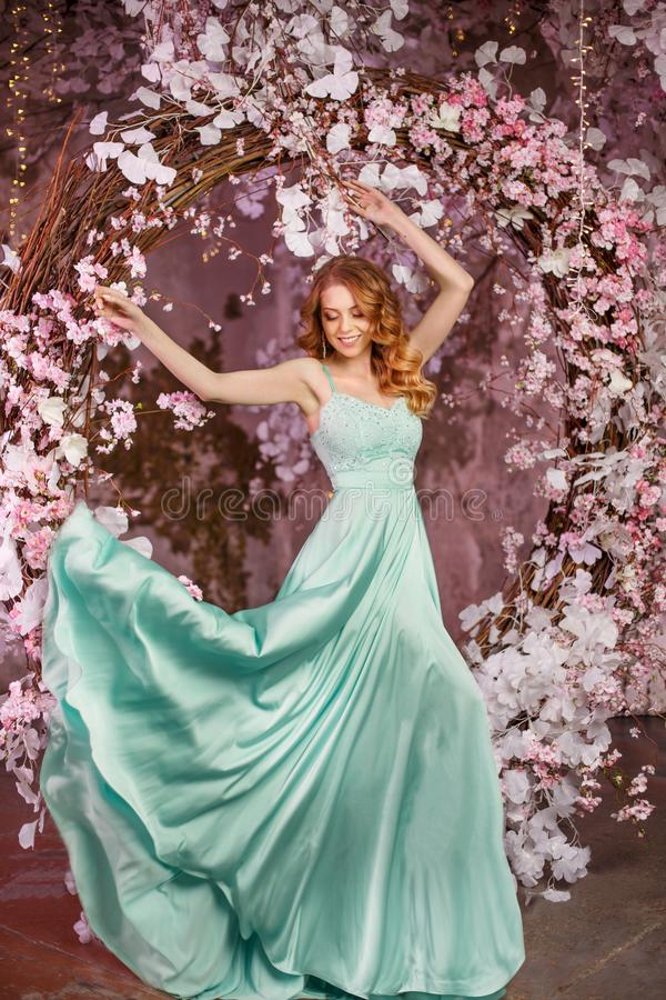 Beautiful woman model in a mint-colored dress on a flowered spring background. Beauty girl with a stunning makeup and hairstyle royalty free stock photography