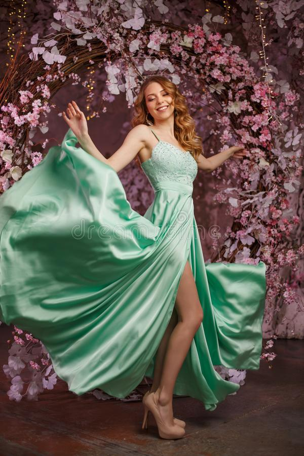 Beautiful woman model in a mint-colored dress on a flowered spring background. Beauty girl with a stunning makeup and hairstyle stock photography