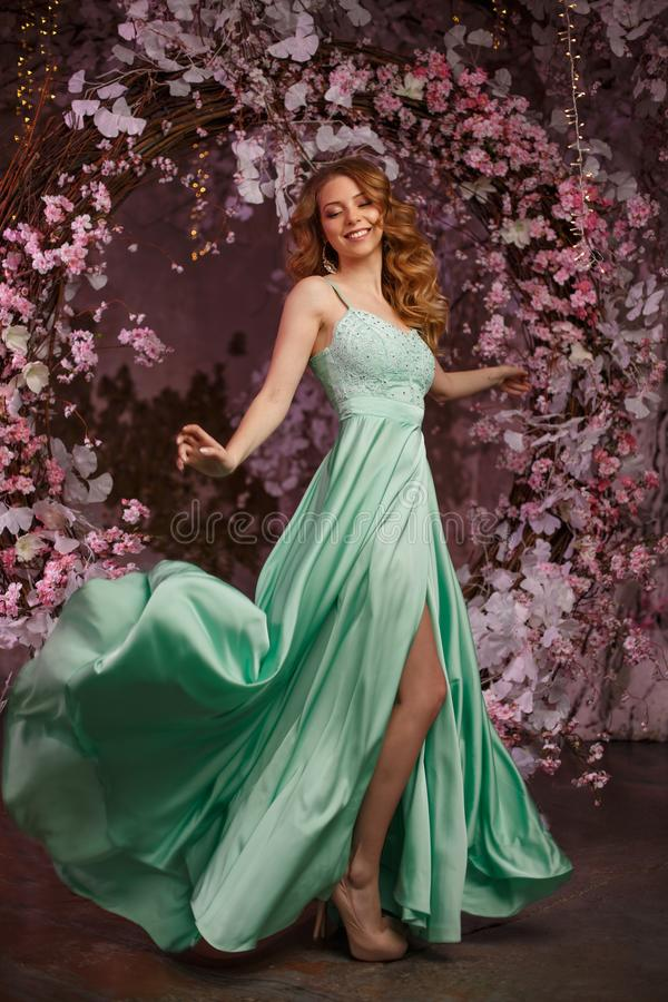 Beautiful woman model in a mint-colored dress on a flowered spring background. Beauty girl with a stunning makeup and hairstyle stock images