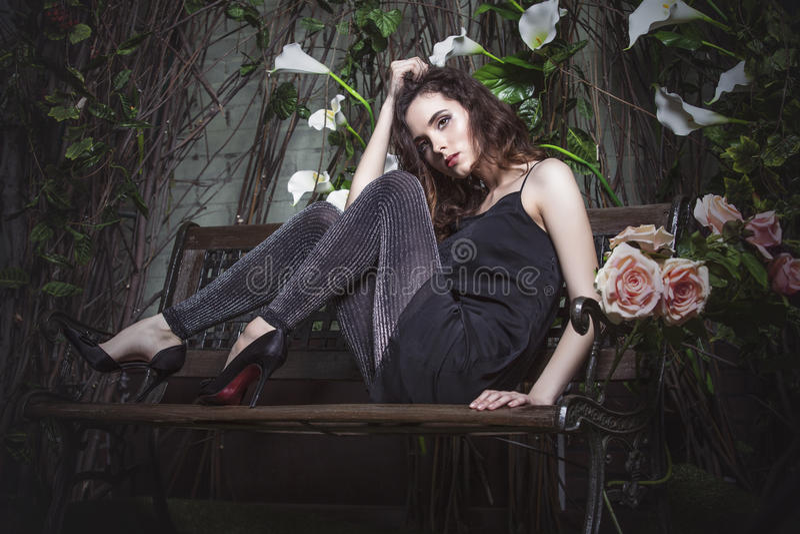 Beautiful woman model in the night garden in stylish dress tunic. Beautiful woman model in the night garden in stylish black dress tunic and leggings royalty free stock photo