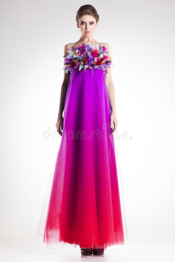 Beautiful woman model posing in long colorful dress with feathers royalty free stock photos