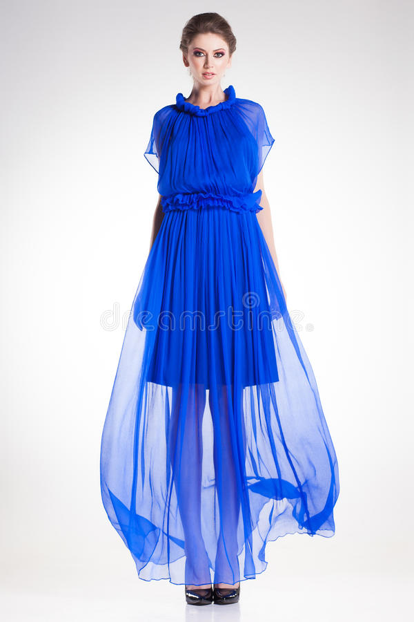 Beautiful woman model posing in long elegant blue silk dress stock images