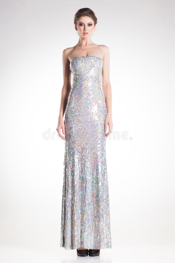 Beautiful woman model posing in long elegant silver sequins dress royalty free stock photography