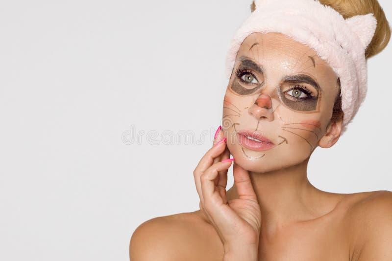 Beautiful woman with moisturizing leopard face mask. Mask with leopard, cat. Beautiful woman model girl with moisturizing leopard face mask. Mask with leopard stock photo