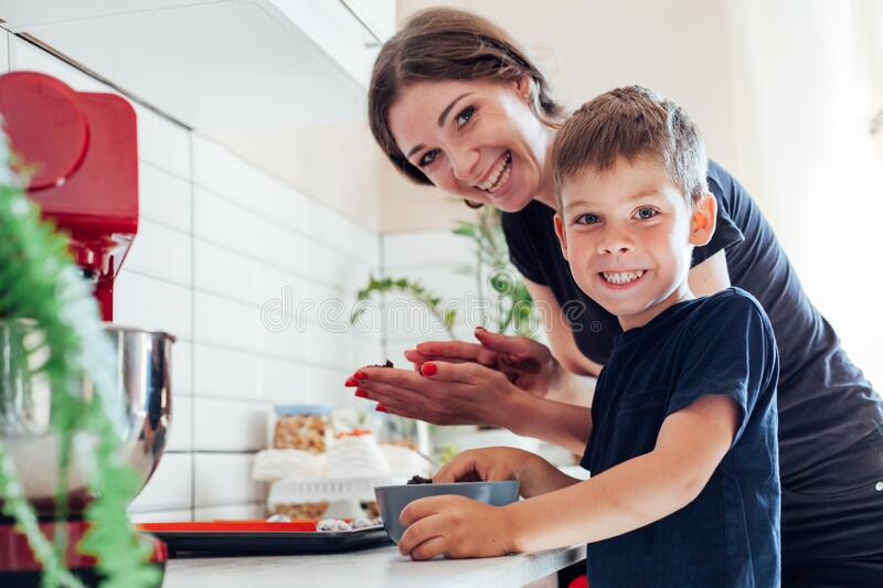 Beautiful woman mom and son together cooks sweet cakes in the kitchen stock photo