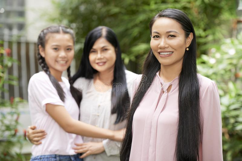 Beautiful woman with mother and daughter. Adult Asian women with mature women and teenage girl on background smiling at camera stock images
