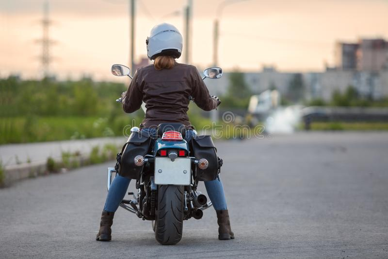 Beautiful woman motorcycle driver waiting on the road at the evening, rear view royalty free stock photography