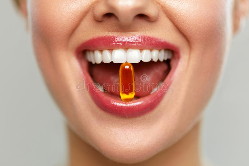 Beautiful Woman Mouth With Pill In Teeth. Girl Taking Vitamins royalty free stock photos