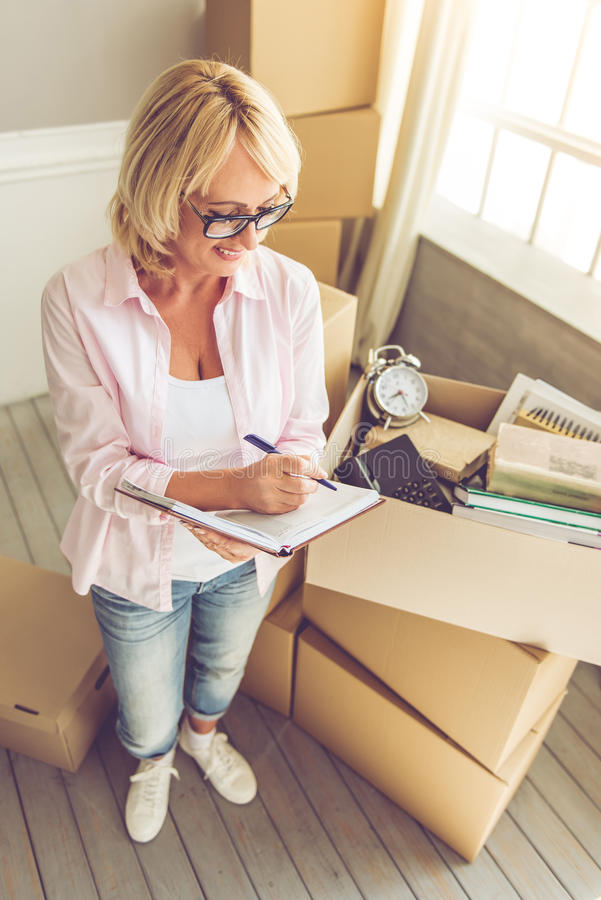 Beautiful woman moving. Beautiful mature woman in casual clothes and eyeglasses is packing her stuff into the boxes, making notes and smiling while moving to the stock photography