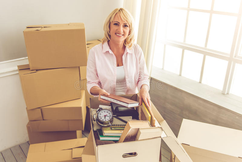 Beautiful woman moving. Beautiful mature woman in casual clothes is packing her stuff into the boxes, looking at camera and smiling while moving to the new royalty free stock photos