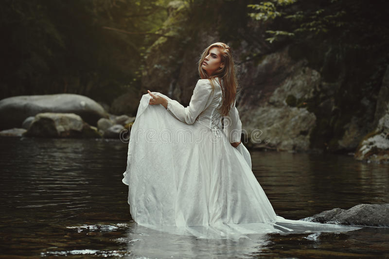 Beautiful woman in mystical waters. Beautiful ethereal woman in mystical waters. Fantasy pond royalty free stock photography