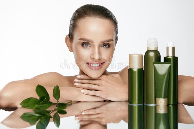 Beautiful Woman With Natural Skin Care Cosmetics. Beautiful Woman With Natural Makeup And Organic Skin Care Cosmetics On White Background. High Resolution stock image