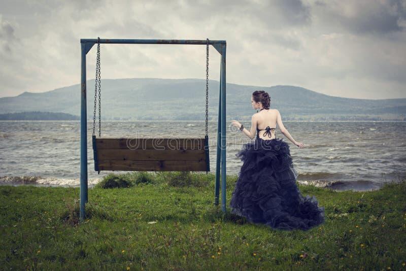 Beautiful woman on nature and swing. stock photo