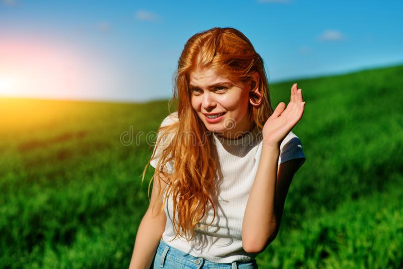 Beautiful woman in the nature tries to understand somebody by trying to hear something with putting her hand to her ears stock images