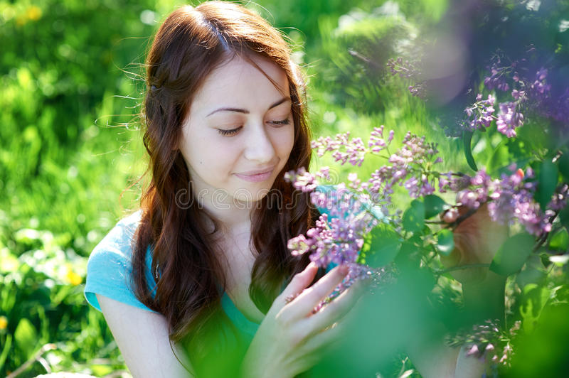 Beautiful woman near the lilac tree in the park stock photo