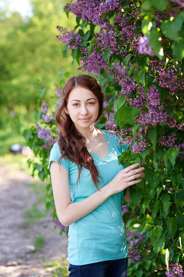 Beautiful woman near the lilac tree in the park stock photos