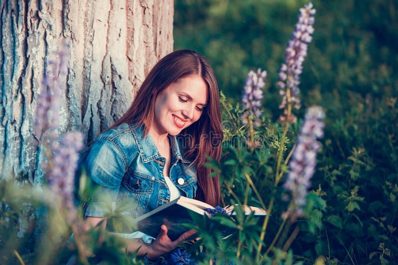 Beautiful woman near the tree and the field with lupine reads a book royalty free stock images