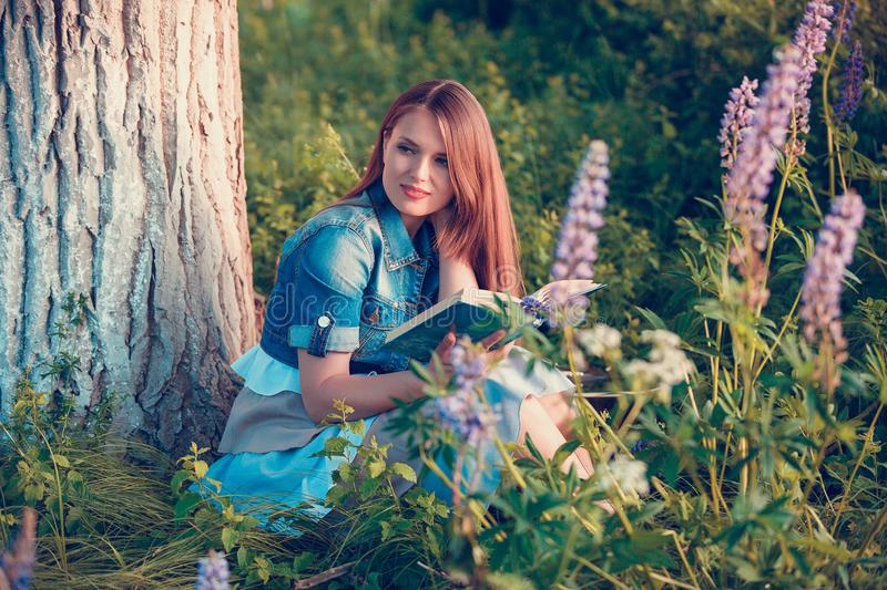 Beautiful woman near the tree and the field with lupine reads a book stock images