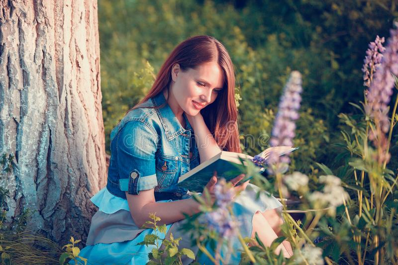 Beautiful woman near the tree and the field with lupine reads a book stock photography