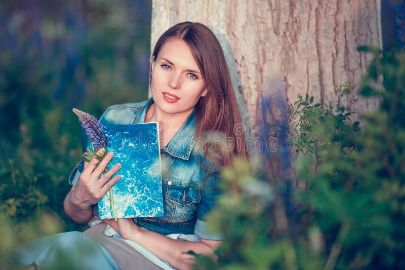 Beautiful woman near the tree and the field with lupine reads a book stock image