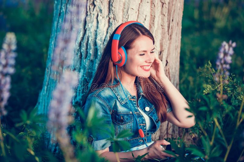 Beautiful woman near the tree and the lupine field is listening to music on headphones and having fun royalty free stock photos
