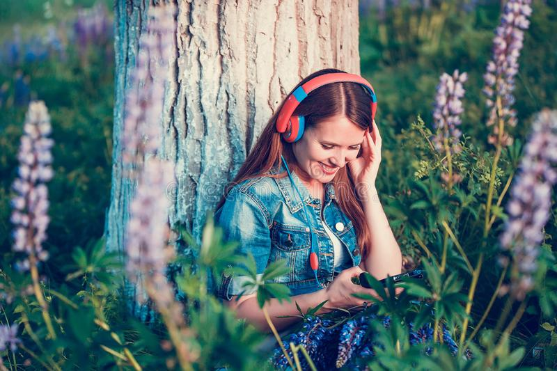 Beautiful woman near the tree and the lupine field is listening to music on headphones and having fun stock photos
