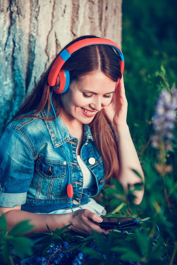 Beautiful woman near the tree and the lupine field is listening to music on headphones and having fun royalty free stock photography