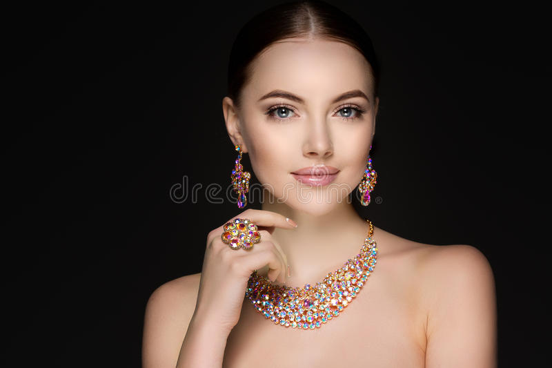 Beautiful woman in a necklace, earrings and ring. Model in jewel. Ry from precious stones, diamonds stock photo
