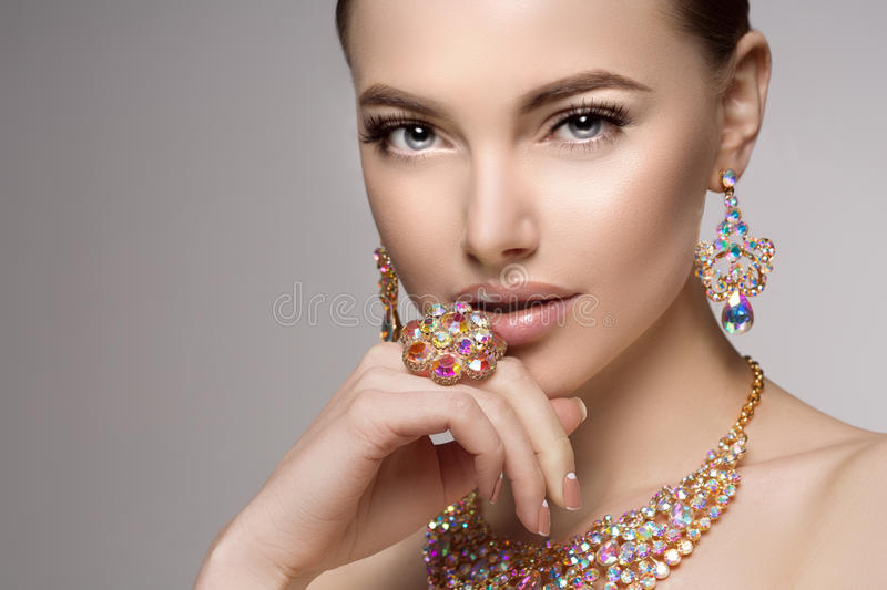 Beautiful woman in a necklace, earrings and ring. Model in jewel royalty free stock image
