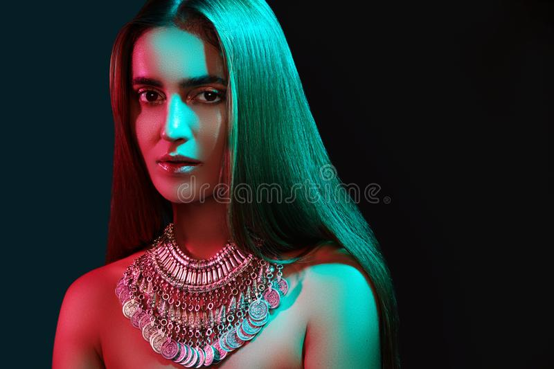 Beautiful woman in a necklace. Model in jewelry from silver. Beautiful indian jewellery. Bright lights. Photo effect stock images
