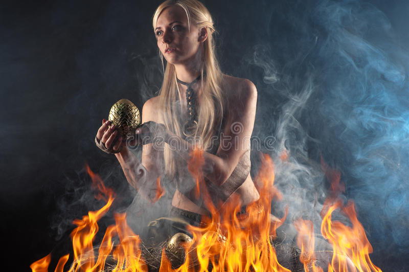 Beautiful woman with a nest egg dragons in the fire. Isolated on black royalty free stock photos