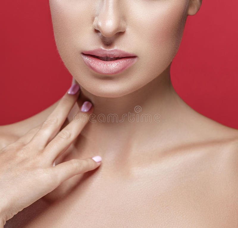 Beautiful woman nose lips and shoulders touching her neck by fingers close up studio portrait on red. Background royalty free stock image