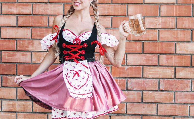 Beautiful woman in Octoberfest dress. Beautiful young woman on stone background in Octoberfest dress royalty free stock image