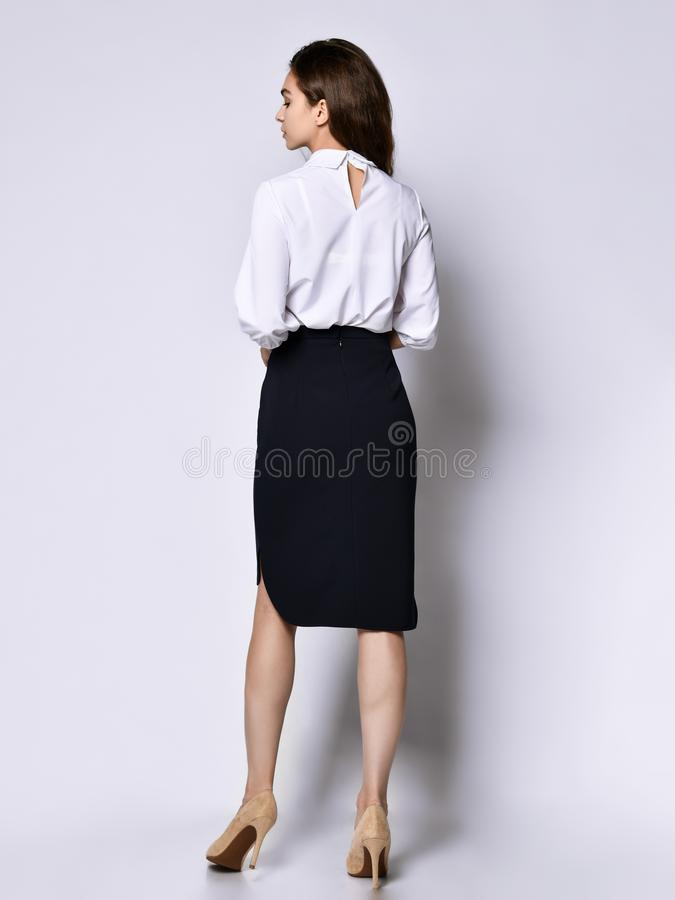 Beautiful woman office manager posing in a new casual white blouse and classic straight dark skirt. Back view of beautiful office manager posing in a new casual stock photo