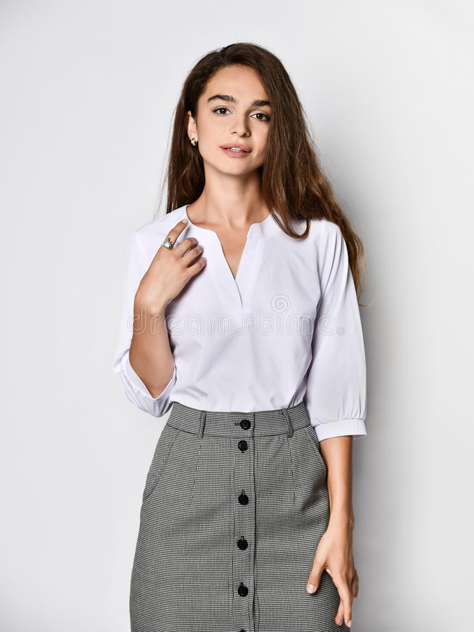 Beautiful woman office manager posing in a new casual white blouse and classic straight dark skirt. Young beautiful woman office manager posing in a new casual stock photo