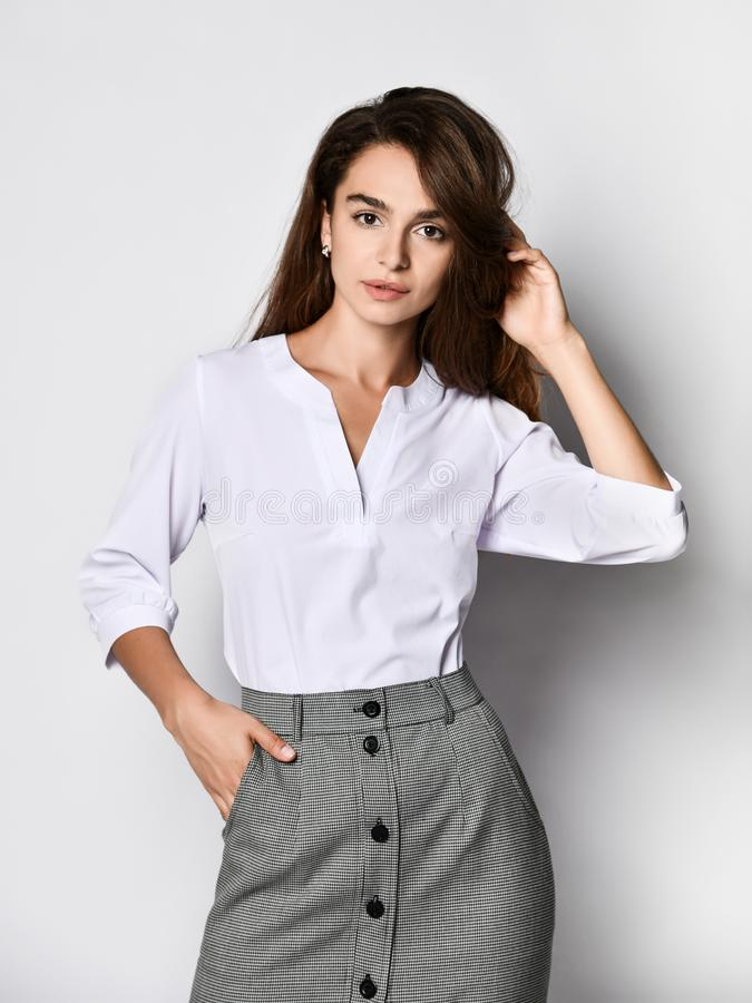 Beautiful woman office manager posing in a new casual white blouse and classic straight dark skirt. Young beautiful woman office manager posing in a new casual royalty free stock photos