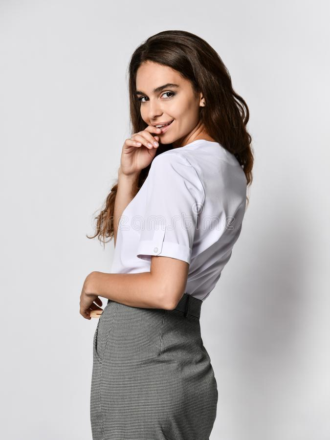 Beautiful woman office manager posing in a new casual white blouse and classic straight dark skirt. Young beautiful office manager smiles at the camera in a new stock images