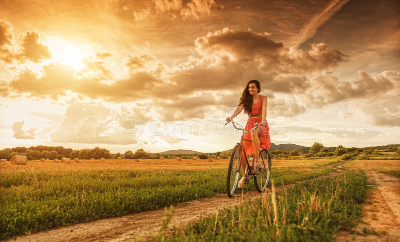 Beautiful woman with old bike in a wheat field royalty free stock photos