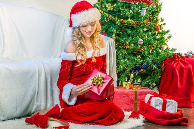 Beautiful woman opening a Christmas gift stock photo