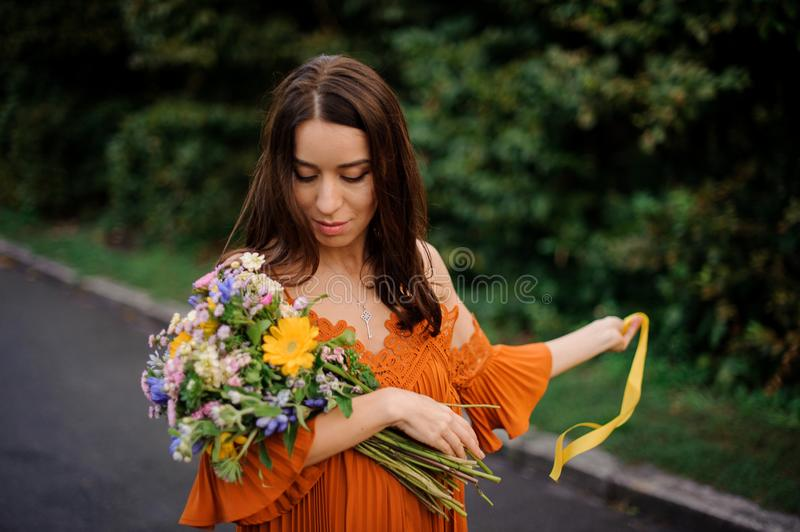 Beautiful woman in orange dress with flowers looks down royalty free stock images