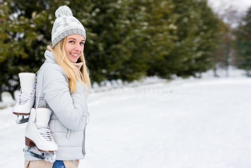 Beautiful woman at outdoor ice-skating rink holding skates. Young beautiful woman at outdoor ice-skating rink holding skates royalty free stock images