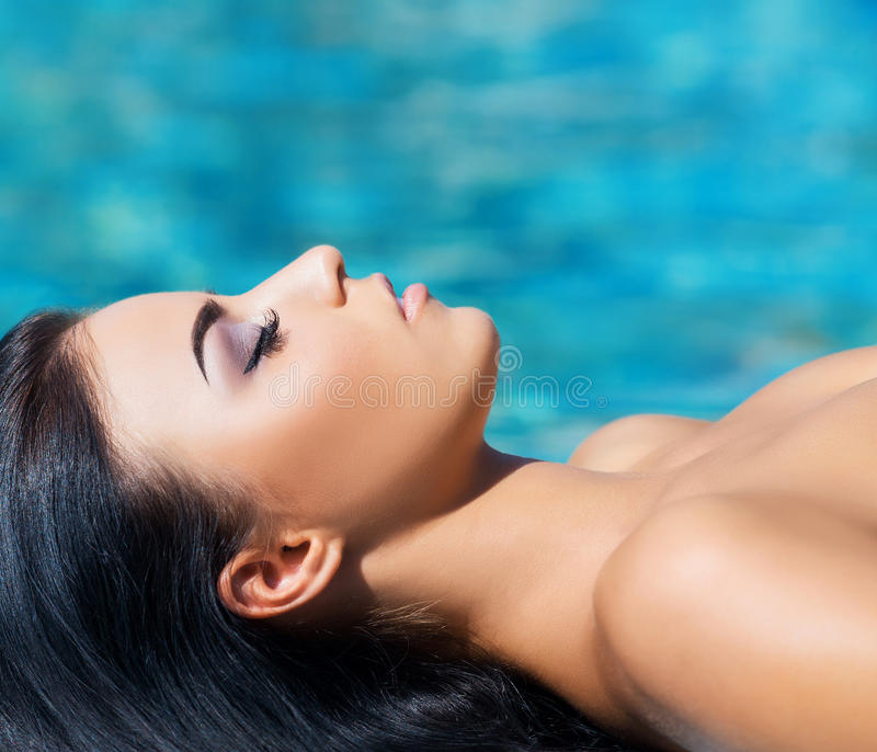 Beautiful woman in an outdoor pool. Spa portrait. stock photo