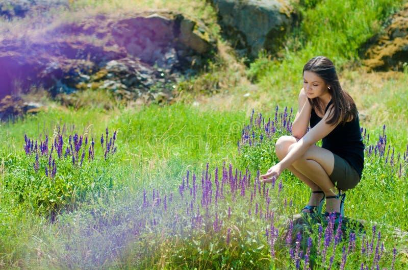 Beautiful woman outdoors & blooming flowers