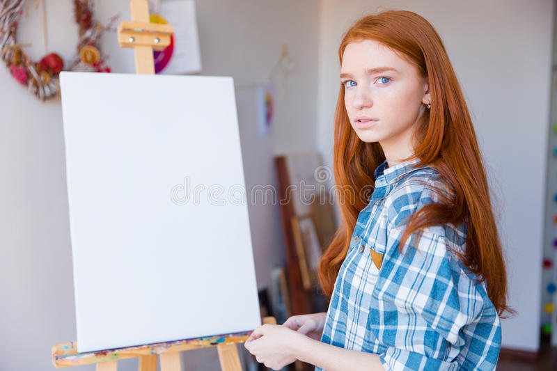 Beautiful woman painter standing near blank easel in art classroom stock photos